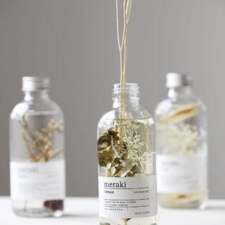 Dekoratívny aróma difuzér vo forme sklenenej fľaštičky s aromatickou tekutinou a ratanovými tyčinkami, ktoré uvoľňujú vôňu v miestnosti.