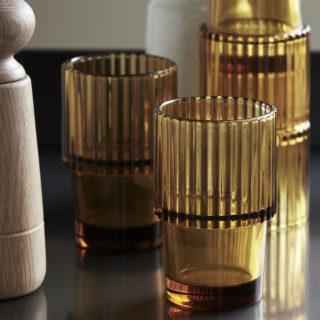 Sklenený pohár s vrchnou polkou rozšírenou a zúbkovanou pre stohovanie pohárov v jantárovej farbe.