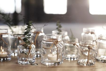 Sklenený držiak na sviečky vo forme skleneného džbánika s hrdlom previazaným koženou šnúrkou.