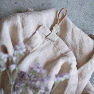 Kovový štipec s koženým uškom pre vešanie textílií, ktoré nemajú vlastné uško.