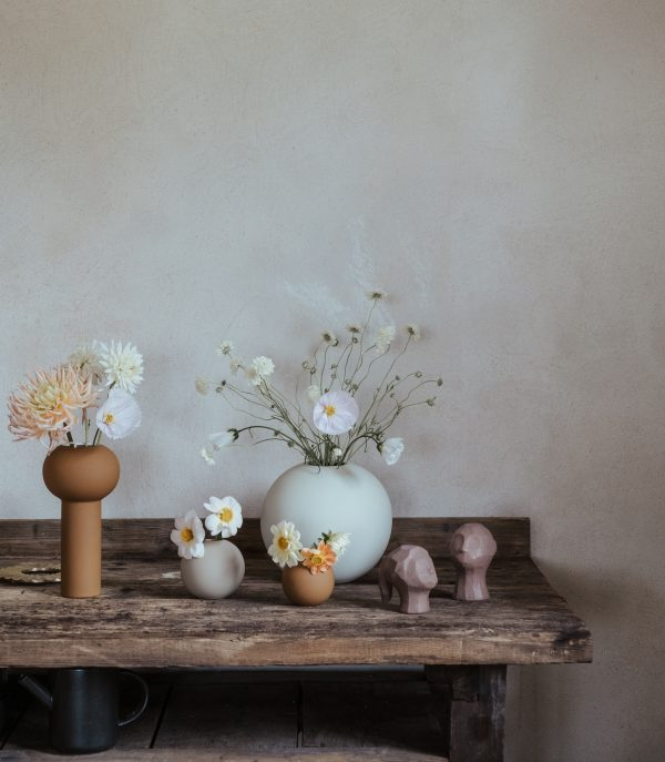 Moderná ručne robená keramická váza s úzkou vysokou nohou v tvare valca zakončená klasickým guľovitým tvarom v béžovej farbe.