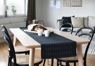 Krásny dizajnový behúň na stôl z organickej bavlny v čiernej farbe s jemnými bielymi prerušovanými pruhmi.