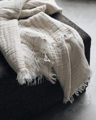 Krásny bavlnený prehoz so strapcami o veľkosti 200 x 140 cm v jemnej béžovej farbe.