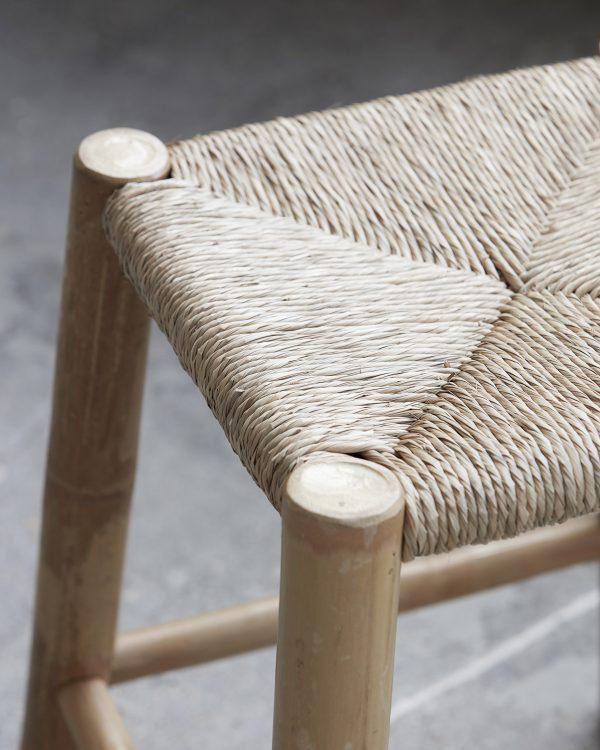 Exotická malá stolička z bambusu na štyroch nôžkach so s vypletaným sedením z morskej trávy.