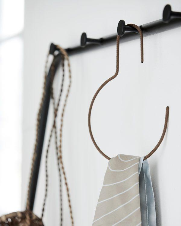 Minimalistický okrúhly kovový vešiak potiahnutý nylónom v hnedej farbe.