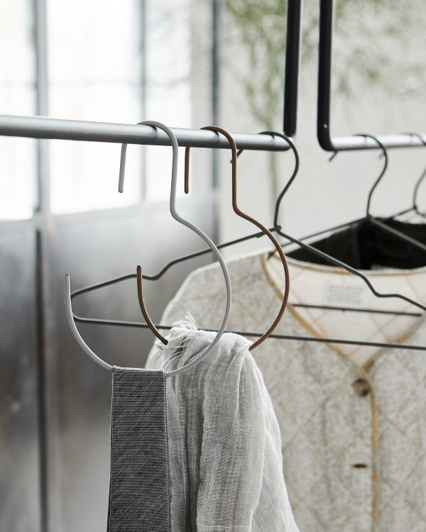 Minimalistický okrúhly kovový vešiak potiahnutý nylónom v sivej farbe.