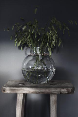 Sklenená priezračná váza v tvare valca s jemným hrdlom previazaným koženou šnúrkou vysoká 25 cm.