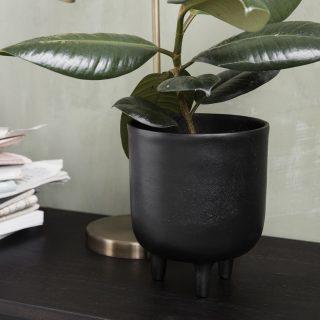 Čierny obal na kvetináč z oxidovaného hliníka na troch nožičkách o priemere 15 cm a výške 18 cm.