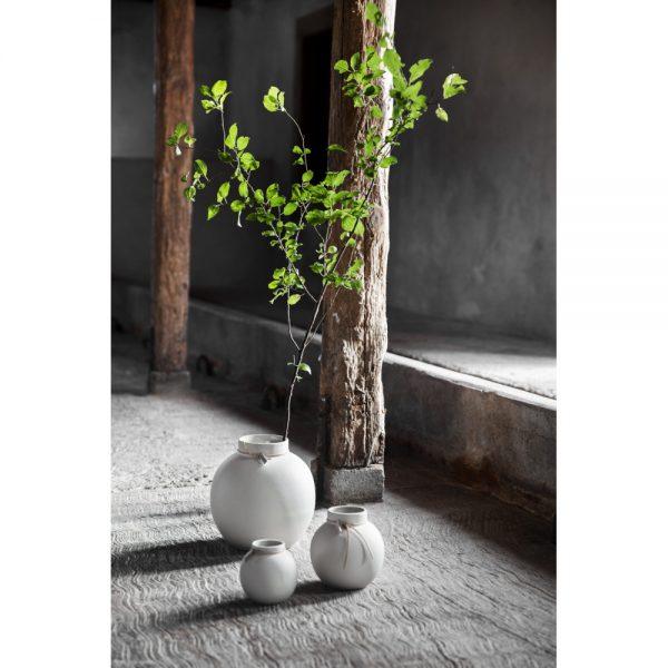 Okrúhla kameninová váza s užším hrdlom previazaným koženou šnúrkou vysoká 13 cm a v bielej farbe.