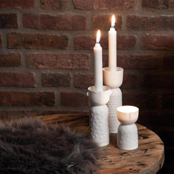 Biely porcelánový svietnik vo tvare valca so šálkou s malými uškami a vrchu, kde sa umiestňuje sviečka. Výška 15 cm.